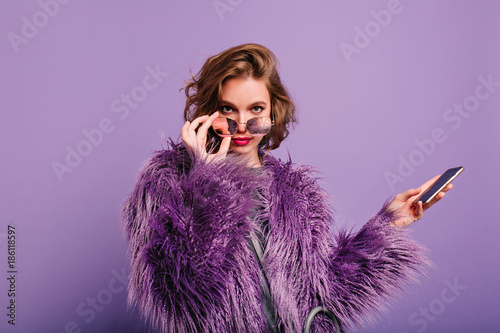 Fotomural  Interested girl in stylish purple fur coat looking to camera holding sparkle sunglasses