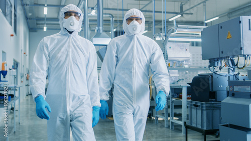 Fényképezés  Two Engineers/ Scientists in Hazmat Sterile Suits Walking Through Technologically Advanced Factory/ Laboratory
