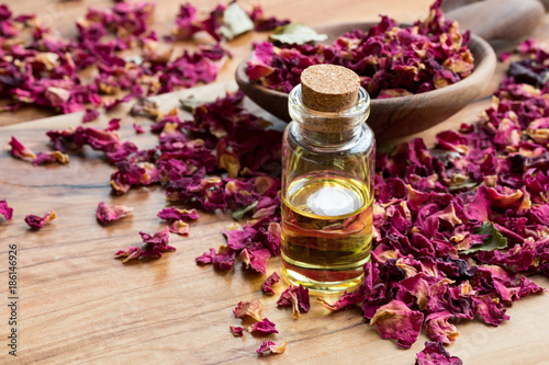 A bottle of rose essential oil with dried rose petals on a