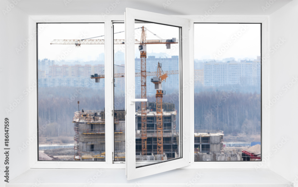 Fototapeta Loud construction site noise immission in opened one frame of pvc window, view through