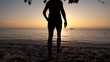 Silhouette of man walking on beach during sunset, super slow motion 240fps