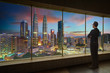 Businessman looking and thinking front of a window office with modern city skyline . Evening scene .