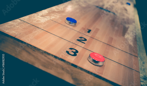Fotografie, Obraz  Vintage shuffle board game with red and blue disc on wooden shuffle table