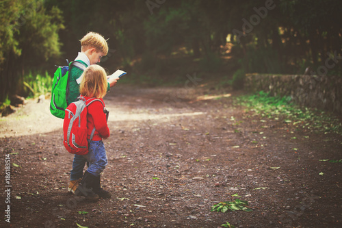 Fotografía  little boy and girl travel hiking in nature looking at map