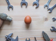 Tool And Egg On Wooden Backgro...