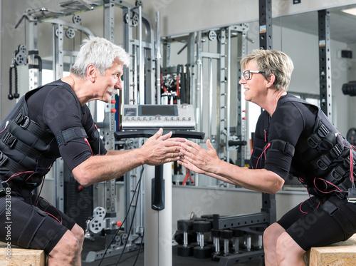 Fotografia, Obraz  Pärchen im mittleren alter trainiert im Fitnessstudio mit einem EMS Gerät Stromi