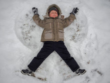 Happy Boy Laying On Snow And M...