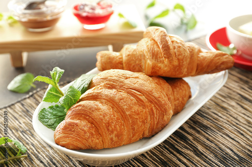 Photo Stands Coffee beans Plate with tasty croissants on table, closeup