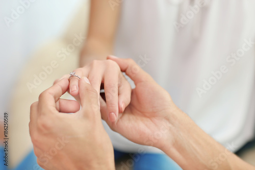 Aluminium Prints Manicure Man putting engagement ring on fiancee's finger indoors