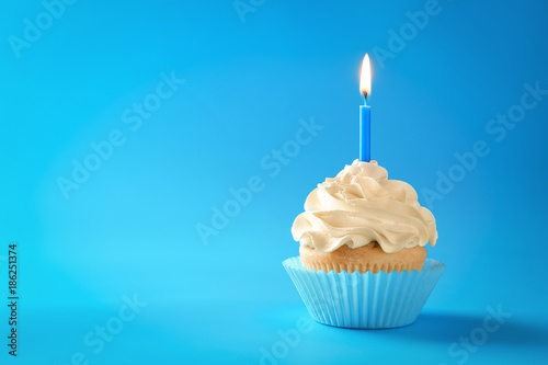 Tasty cupcake with candle on color background Wallpaper Mural
