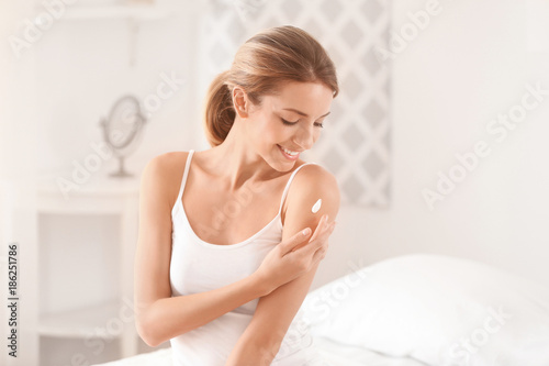 Fototapeta  Young woman applying body cream at home