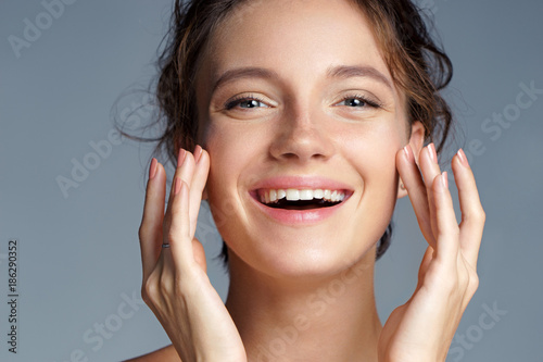 Cuadros en Lienzo  Image with beautiful brunette girl touching her face on grey background
