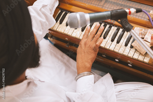 Fototapeta One Punjabi Singer with black turban is playing harmonium and singing at Gurudwa