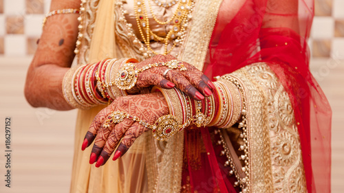 Beautiful female hands of an Indian bride with mehndi and jewelry during a typical Hindu wedding.