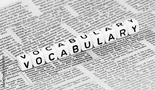 Fotografie, Obraz  Vocabulary alphabet cubes on newspaper