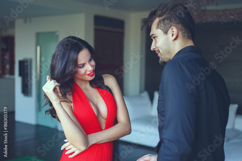 Woman in red dress and lis flirting with young man indoors Tablou Canvas