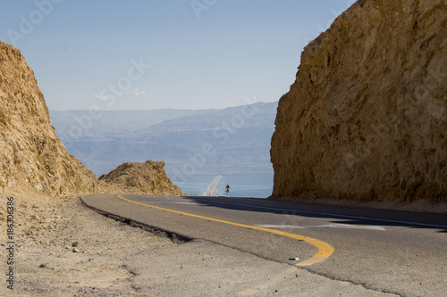 Fotobehang Midden Oosten a desert road among the rocks to the coast of the Dead Sea against the Judean mountains in the distance