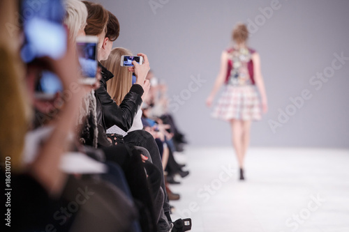 Woman taking picture of new model on fashion show Tablou Canvas