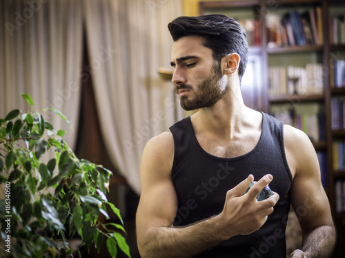 Poster  Handsome muscular young man in his home spraying cologne or perfume on neck