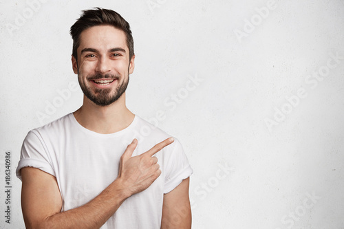 Fototapeta Horizontal portrait of bearded cheerful man has smile, wears casual white t shirt, indicates with fore finger at copy space for your promotional text or advertisment, isolated over concrete wall obraz