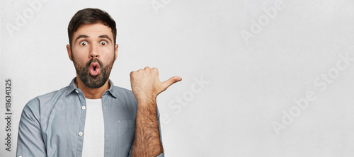 Fotografie, Obraz  Horizontal shot of amazed young man has thick dark beard, dressed in fashionable