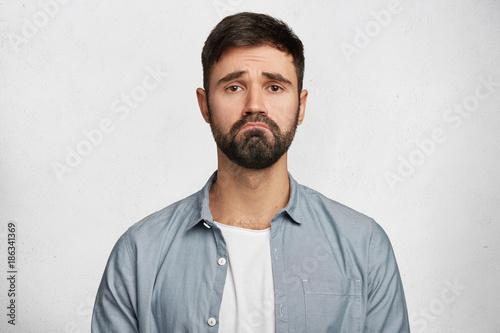 Obraz na plátně  Horizontal shot of attractive male model with unhappy expression curves lips as feels frustration, being upset to hear bad news, isolated over white background