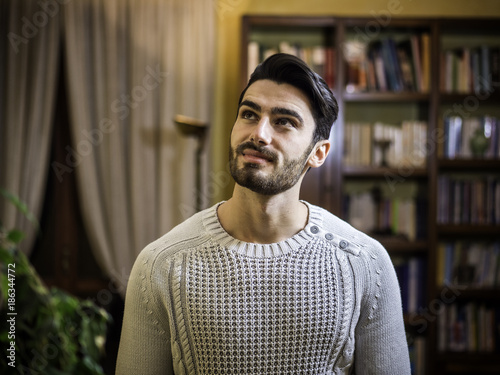 Fototapety, obrazy: Young man with dreamy expression, looking up, standing in living room at home