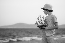 The Boy Stands On The Seashore, Holds A Toy Sailboat In His Hands And Looks Into The Distance. Black And White.