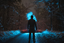 The Man Smoke On The Snowy Road In The Dark Forest. Evening Night Time