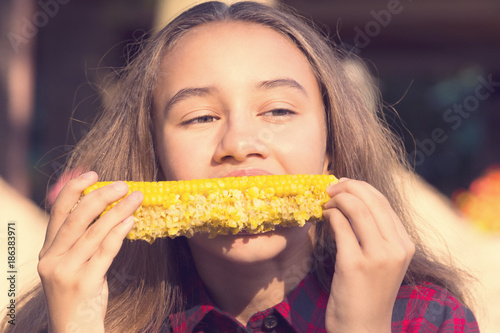 Fotografía  Girl eating sweet corn on the nature of the day