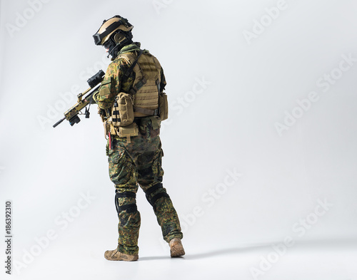 Fotografía  Full length side view serene defender in army clothes keeping assault rifle