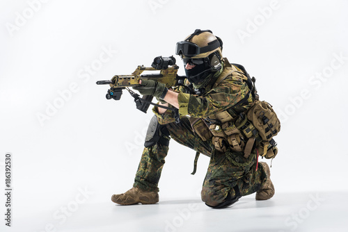 Full length side view severe defender in army clothes looking at sniper scope Wallpaper Mural
