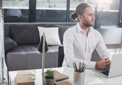 Obraz na plátně  Thoughtful man sitting at the table near laptop