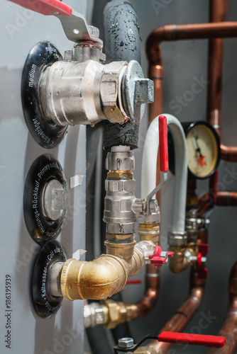 Photo Valves and copper pipes on a boiler in a boiler room