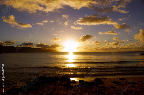 Sunset over the ocean with waves moving to shore