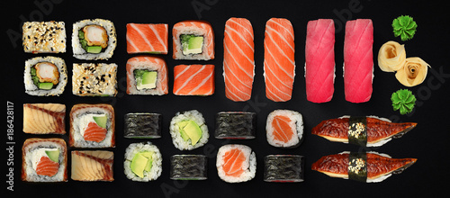 Photo Stands Sushi bar Japanese cuisine. Sushi and rolls set over dark background.