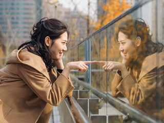Beautiful Chinese girl looking at her mirror image in glass.