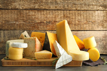 Wooden Board With Different Kinds Of Delicious Cheese On Table