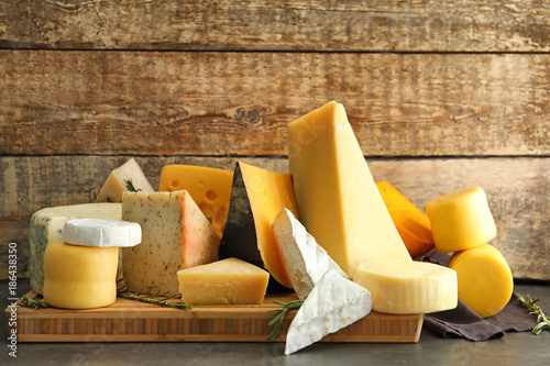 Wooden board with different kinds of delicious cheese on table Fototapet