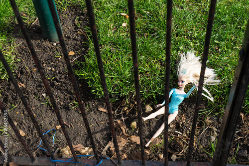 Photo Lost doll lying behind a fence in the park