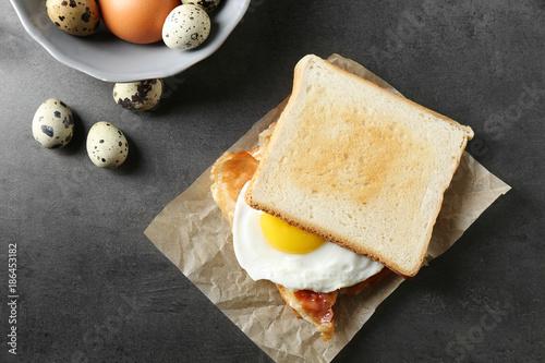 Foto op Plexiglas Gebakken Eieren Tasty toast with fried egg and bacon on table