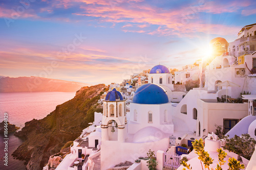Canvas Prints Light pink Sunset view of the blue dome churches of Santorini, Greece.