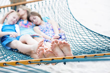 Family Relaxing Together On A Hammock, Focus On Feet