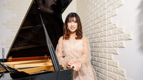 Fotografie, Obraz  Chinese girl and grand piano. Beautiful young girl pianist.