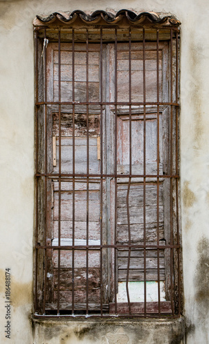 Old unpainted white shutters in window behind rusted iron bars on unpainted whit Canvas Print