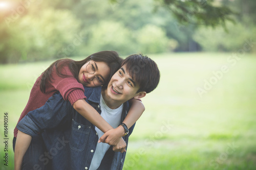 Fotografie, Obraz  Couple of love, a man carry a girl on his back in park