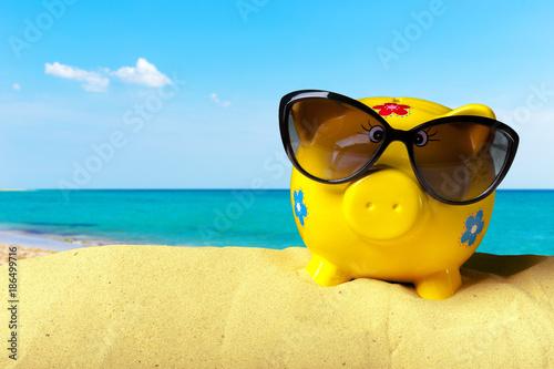 Fototapeta Piggy bank on a beach. Vacation savings concept obraz