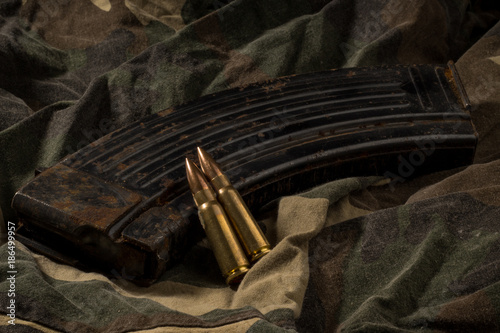 Rusty AK-47 magazine and bullets on camouflage textile background Canvas Print