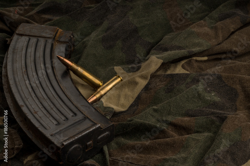 Rusty AK-47 magazine and bullets on camouflage textile background Fototapet
