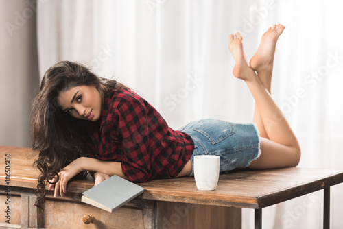 Photo sensual young woman with book lying on table with cup of coffee and looking at c
